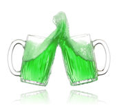 St. Patrick's Day green beer. Pair of green beer glasses making a toast. St. Patrick's Day beer splash Royalty Free Stock Images