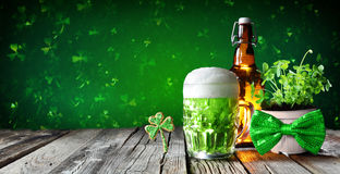 St Patrick`s Day - Green Beer In Glass With Bottle And Clovers. On Wooden Table stock photo