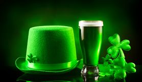 St. Patrick`s Day. Green beer pint and leprechaun hat over dark green background. Decorated with shamrock leaves. Traditional Irish festival Royalty Free Stock Photos