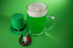 St Patrick`s Day green beer with shamrock, horseshoe and Leprechaun hat against green background. Royalty Free Stock Photography