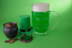 St Patrick`s Day green beer with shamrock, pot with gold coins, horseshoe and Leprechaun hat against green background. Stock Photos