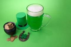 St Patrick`s Day green beer with shamrock, pot with gold coins, horseshoe and Leprechaun hat against green background. Stock Images