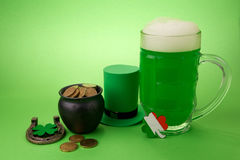 St Patrick`s Day green beer with shamrock, pot with gold coins, horseshoe and Leprechaun hat against green background. Stock Photo