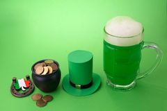 St Patrick`s Day green beer with shamrock, pot with gold coins, horseshoe and Leprechaun hat against green background. Stock Photography