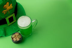 St Patrick`s Day green beer with shamrock, pot with gold coins, horseshoe and Leprechaun hat against green background. Stock Image