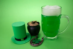 St Patrick`s Day green beer with shamrock, pot with gold coins, horseshoe and Leprechaun hat against green background. Royalty Free Stock Image