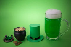 St Patrick`s Day green beer with shamrock, pot with gold coins, horseshoe and Leprechaun hat against green background. Royalty Free Stock Photos