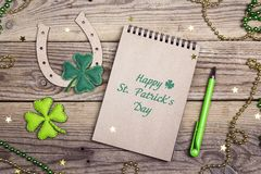 St.Patrick`s day greeting message with horseshoe and felt clover. Leaves on wooden boards. St.Patrick`s day holiday symbol royalty free stock image