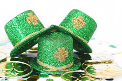 St. Patrick's Day Hat Trio. Three green glitter hats with gold shamrocks on them with gold coins and confetti for St. Patrick's Day Royalty Free Stock Photos