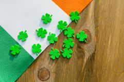 St Patrick`s Day holiday background. Green quatrefoils above the Irish national flag on the wooden background. St Patrick`s day festive holiday concept royalty free stock photo