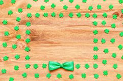 St Patrick`s Day holiday background, green quatrefoils and bow tie on the wooden background with border. And free space stock photography