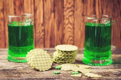 St. Patrick`s day holiday, green beer in two mugs with snacks. Stock Image