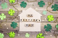 St.Patrick`s day home symbol with clover leafs on wooden backgro. St.Patrick`s day home symbol with four-leaf clover on wooden background Royalty Free Stock Images