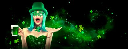 St. Patrick`s Day. Leprechaun model girl with pint of green beer over dark green background, decorated with shamrock leaves stock image