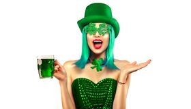 St. Patrick`s Day. Leprechaun model girl with pint of green beer over white background. Patrick Day royalty free stock photo