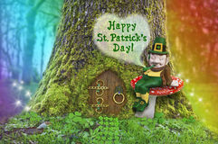 St. Patrick`s Day leprechaun on a mushroom in forest with rainbow. St. Patrick`s Day text with Leprechaun sitting on a mushroom in front of a tree with a fairy Stock Image