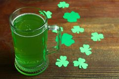 St.Patrick `s Day. Mug of green beer and clover on a wooden background. Concept day of St. Patrick Stock Photo
