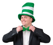 St. Patrick's Day Outfit 2. Young man wearing suit with green novelty hat, straightening green bow tie for St. Patrick's Day. Isolated Stock Image