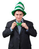 St. Patrick's Day Outfit 4. Young man wearing suit with green novelty hat, straightening green bow tie for St. Patrick's Day. Isolated Stock Photos