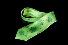 St. Patrick's Day shamrock tie. Green St. Patrick's day tie curled up with green shamrocks all over it against a black low key background with reflection Royalty Free Stock Photography