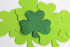St. Patrick's Day Shamrocks. A sparkling Shamrock on top of light green shamrocks with white background royalty free stock photos