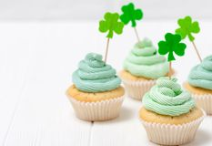 St. Patrick`s Day theme colorful horizontal banner. Cupcakes decorated with green buttercream and craft felt decorations in form. Of shamrock leaves on white Stock Photos