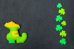 St. Patrick`s Day theme colorful horizontal banner. Green leprechaun hand made shoe with gold and shamrock leaves on black backgr. Ound. Felt craft elements royalty free stock images