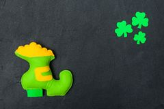 St. Patrick`s Day theme colorful horizontal banner. Green leprechaun hand made shoe with gold and shamrock leaves on black backgr. Ound. Felt craft elements royalty free stock photos