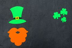 St. Patrick`s Day theme colorful horizontal banner. Green leprechaun hat, beard and shamrock leaves on black background. Felt cra. Ft elements. Copy space. For royalty free stock photos