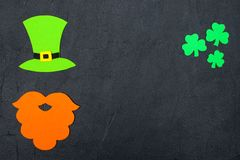St. Patrick`s Day theme colorful horizontal banner. Green leprechaun hat, beard and shamrock leaves on black background. Felt cra. Ft elements. Copy space. For stock photo