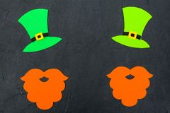 St. Patrick`s Day theme colorful horizontal banner. Green leprechaun hat, beard and shamrock leaves on black background. Felt cra. Ft elements. Copy space. For royalty free stock photography
