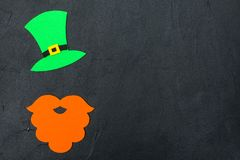 St. Patrick`s Day theme colorful horizontal banner. Green leprechaun hat, beard and shamrock leaves on black background. Felt cra. Ft elements. Copy space. For royalty free stock photo
