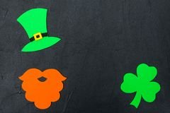 St. Patrick`s Day theme colorful horizontal banner. Green leprechaun hat, beard and shamrock leaves on black background. Felt cra. Ft elements. Copy space. For stock images