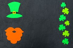 St. Patrick`s Day theme colorful horizontal banner. Green leprechaun hat, beard and shamrock leaves on black background. Felt cra. Ft elements. Copy space. For stock photography