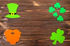 St. Patrick`s Day theme colorful horizontal banner. Green leprechaun hat, beard and shamrock leaves on brown wooden background. F. Elt craft elements. Copy space Stock Images