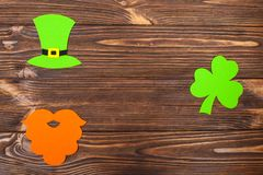 St. Patrick`s Day theme colorful horizontal banner. Green leprechaun hat, beard and shamrock leaves on brown wooden background. F. Elt craft elements. Copy space Stock Photography