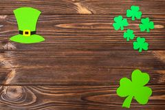St. Patrick`s Day theme colorful horizontal banner. Green leprechaun hat and shamrock leaves on brown wooden background. Felt cra. Ft elements. Copy space. For Royalty Free Stock Image