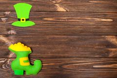 St. Patrick`s Day theme colorful horizontal banner. Green leprechaun hat and shoe with gold on brown wooden background. Felt cref. St. Patrick`s Day theme Stock Photography