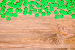 St Patrick`s Day background with one side border of green quatrefoils and free space for text. St Patrick`s Day wooden background with one side border of green stock photo