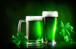 St Patrick ` s dzień Zielony piwny pół kwarty nad ciemnozielonym tłem, dekorującym z shamrock opuszcza zdjęcie royalty free