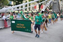 St- Patrick` s Tages-Gaelic Dragon-Team, welches die Cavengah-Brücke in Singapur kreuzt Lizenzfreie Stockfotografie