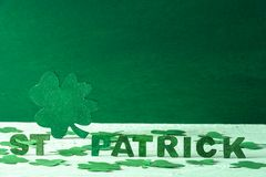 St Patrick words and green shamrock. The words St Patrick written in green wooden letters and a big green clover in the back, surrounded by paper shamrocks, on a Stock Image