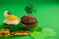 St Patricks在杯形蛋糕的天三叶草与金币 图库摄影