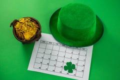 St Patricks天有三叶草、日历和罐的妖精帽子有巧克力金币的 免版税图库摄影