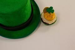 St Patricks天有三叶草的妖精帽子在杯形蛋糕 图库摄影