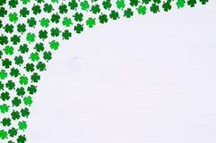St Patricks天背景-一边弯曲了绿色quatrefoils边界白色木表面上的 免版税库存图片