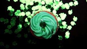 St patricks旋转与绿色三叶草五彩纸屑落的天杯形蛋糕 股票录像