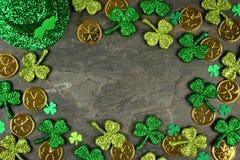 St Patricks Dagkader van klavers, gouden muntstukken & kabouterhoed over een donkere achtergrond royalty-vrije stock foto