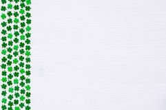 St Patricks Day background with border of green quatrefoils. St Patricks Day background - one side border of dark green quatrefoils on the white wooden surface royalty free stock images