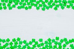 St Patricks Day background with both side borders and green quatrefoils. St Patricks Day background - both side borders of green quatrefoils on the white wooden royalty free stock photos